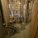 View of the utiity room with sewage pump and new bath beyond.